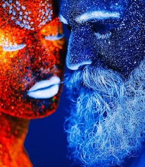 Concept. portrait of a bearded man and woman painted in ultraviolet powder.