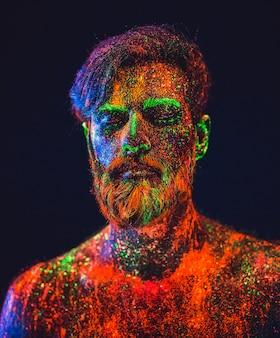 Концепция. портрет бородатого мужчины. человек окрашен в ультрафиолетовую пудру.