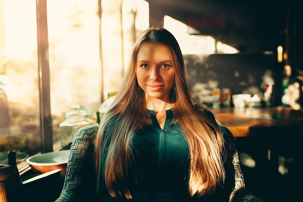 해질녘 카페의 소파에 앉아 있는 아름다운 젊은 여성의 개념 초상화