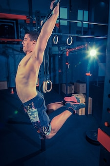 Concept power strength healthy lifestyle sport powerful attractive muscular man at crossfit gym