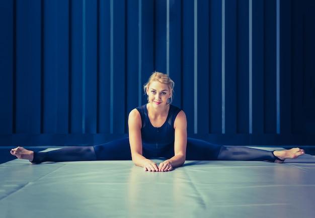 Понятие: сила, сила, здоровый образ жизни, спорт. мощная привлекательная мускулистая женщина-тренер crossfit делает упражнения на растяжку или растягивает шпагат во время тренировки в тренажерном зале