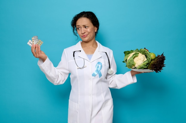 Concept of proper nutrition and health care. confident female doctor in medical gown with blue diabetes awareness ribbon holds a plate of healthy vegan food and blister with medications in her hands.