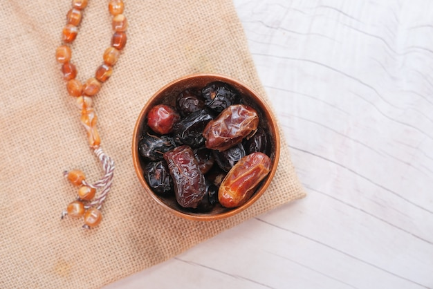 The concept of ramadan, fresh date fruit in a bowl on table .