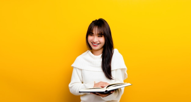 The concept of reading books increases knowledge, increases concentration. woman reading a book cute asian woman smiling happily. on a yellow background