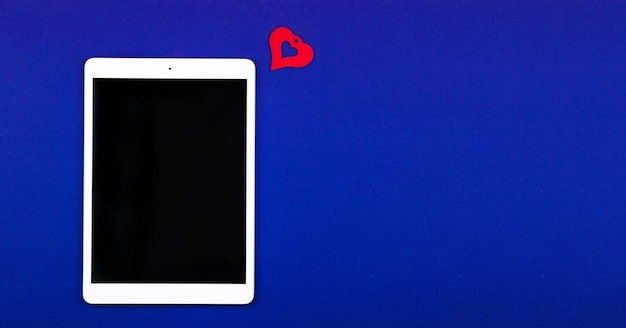 Concept of receiveing new likes and followers, tablet on blue background with copy space. high quality photo