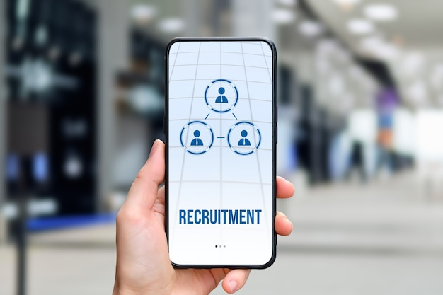The concept of recruitment on the phone, which holds the person in the background of the business office.