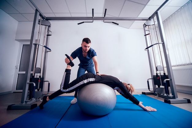 Concept of rehabilitation. beautiful young woman doing exercises with ball under supervision of physiotherapist