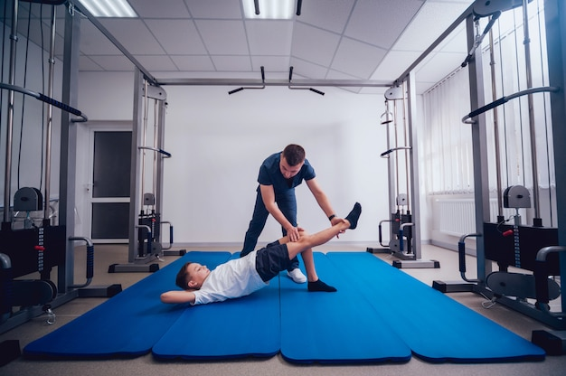 Concept of rehabilitation. young boy doing exercises on mat under supervision of physiotherapist