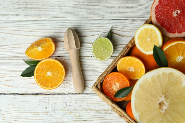 Concept of ripe food with different citrus on white wooden table