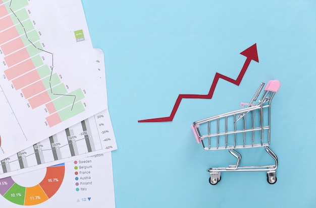 The concept of rising sales. shopping trolley with growth arrow, graphs and charts on blue