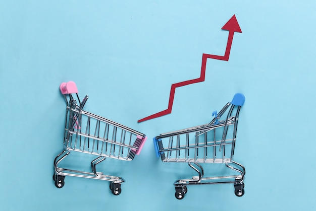 The concept of rising sales. shopping trolleys with growth arrows on blue