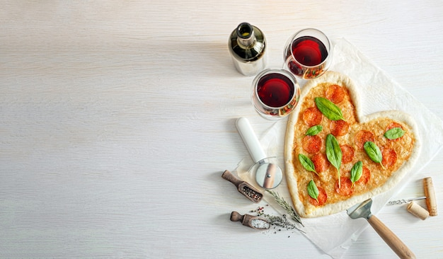 Concept of romantic dinner for two with red wine and pizza in the shape of a heart. dinner for valentine's day