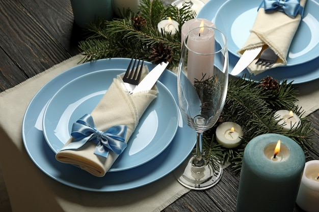 Concept of romantic new year table setting with candles on wooden table