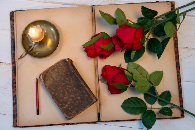 Concept romantic, old notebook, roses and small candle