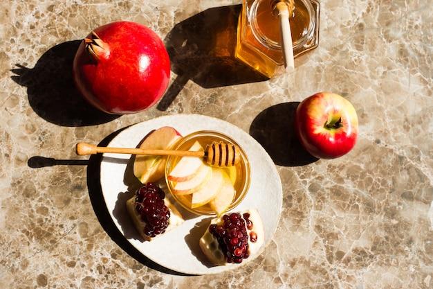 Концепция рош ха-шана открытка с яблоками, гранатами и медом на мраморном фоне