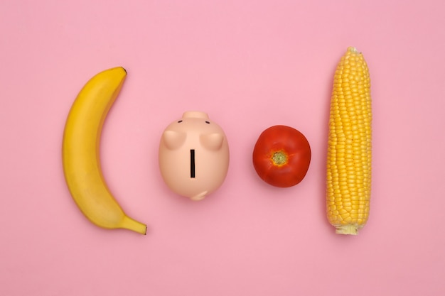 The concept of saving on food. piggy bank, vegetables and fruits on a pink background. minimalism composition
