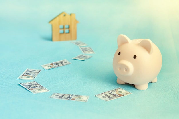 The concept of saving money to buy an apartment, house or other residential property. piggy bank and wooden house on a blue background.