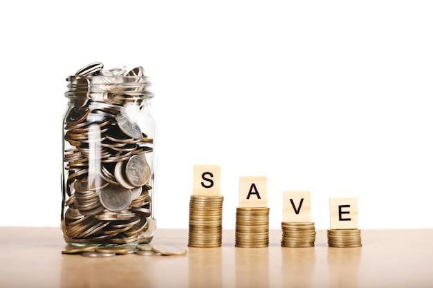 Концепция экономии денег на будущее. монеты в стеклянной банке на белом фоне для финансовой экономии денег