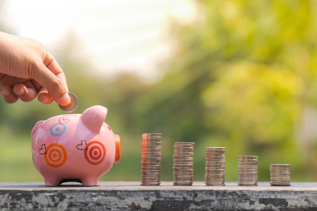 The concept of saving money, hand putting a coin into piggy bank over blurred garden background