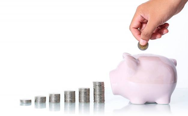 The concept of saving money, hand putting a coin into piggy bank on white
