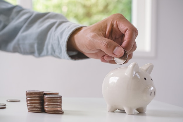 Concept saving money for wealth. close up view person putting coin into piggy bank.