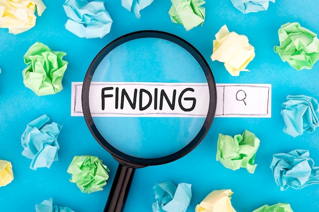 Concept of searching. text finding with magnifier and pieces of paper on blue background.