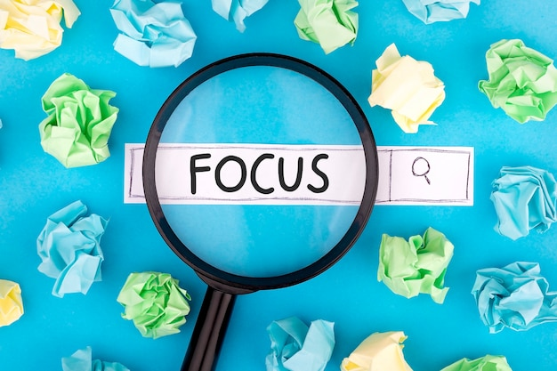 Concept of searching. text focus with magnifier and pieces of paper on blue background.