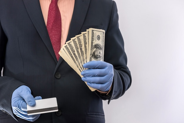 Concept of security when paying for a product or service, businessman holding money and credit card in gloves. covid19 coronavirus