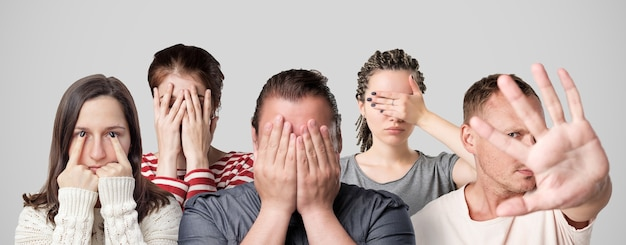 Concept of shame or guilt. group of people closing their face or eyes with hands