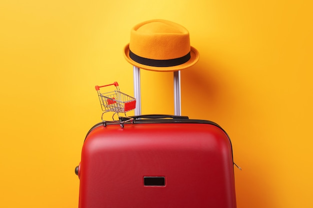Concept of shopping abroad, hat at suitcase with shopping cart over trend yellow background