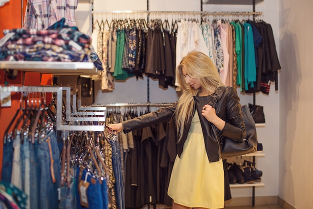 Concept shopping. portrait of beauty smiling woman in shop, choosing clothes.