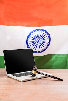 Concept showing indian and cyber law with laptop, wooden gavel or hammer and tricolour flag in the background