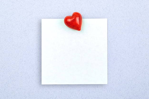 Concept of simple love letter, pinned notepad papaer with red heart on a light blue background, copy space photo