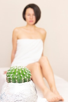 Concept of smooth beautiful skin without extra hair. a beautiful girl sits and looks at a cactus. depilation. no to hair