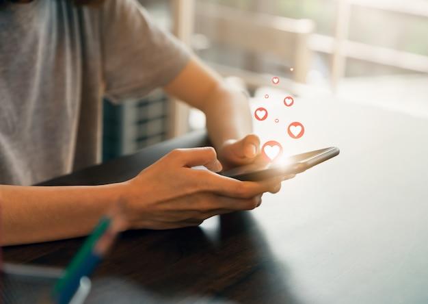 概念のソーシャルネットワーク。女性ハンドプレス電話と携帯電話にハートのアイコンを表示します。