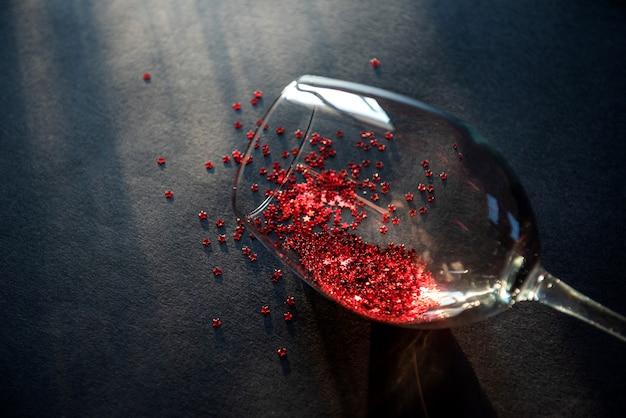 コンセプトは赤ワインをこぼした。パーティーの終わり。こぼれたワインを象徴する赤い星のテーブルの上に横たわるワインのグラス