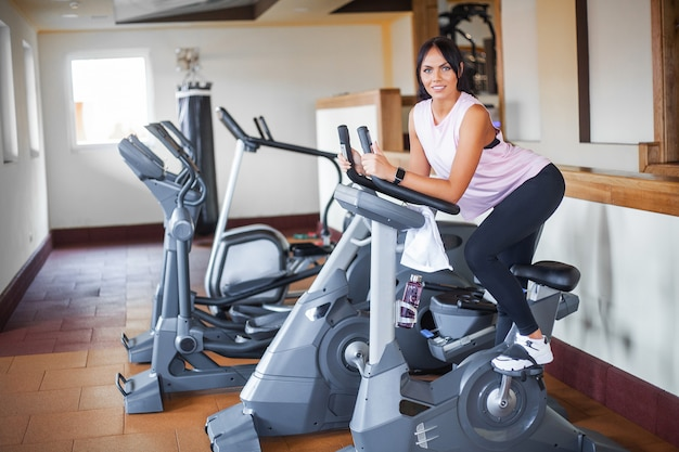 Concept of sport and healthy lifestyle. exercising legs doing cardio workout on cycling bike