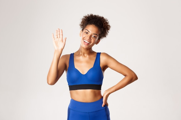 Concept of sport and workout. attractive, healthy african-american female athlete, waving hand