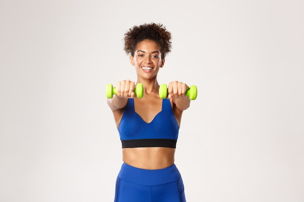 Concept of sport and workout. smiling attractive fitness woman in blue gym clothing, lifting