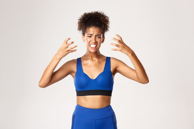 Concept of sport and workout. waist-up of distressed young african-american fitness woman in blue