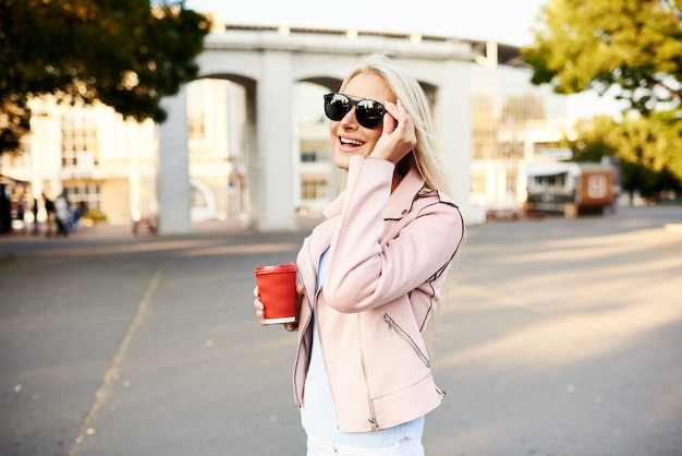 Concept of street fashion. young stylish girl student walking in the sunny park and holds a cup of coffee to go.