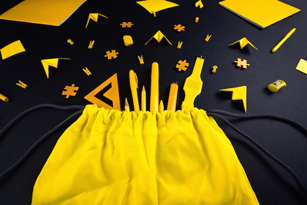 A concept on the subject back to school. the student's yellow stationery on a black background.