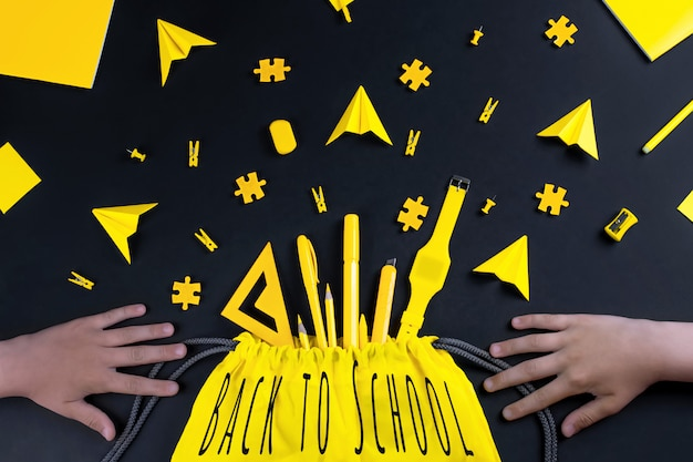 A concept on the subject back to school with hands. the student's yellow stationery on a black background.