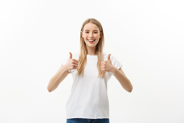Concept of success happy student. portrait of attractive smile teenage girl show thumbs up gesture, in white shirt, isolated over white background.