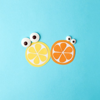 Concept of summer - two fruit from paper with cute eyes - lemon and orange