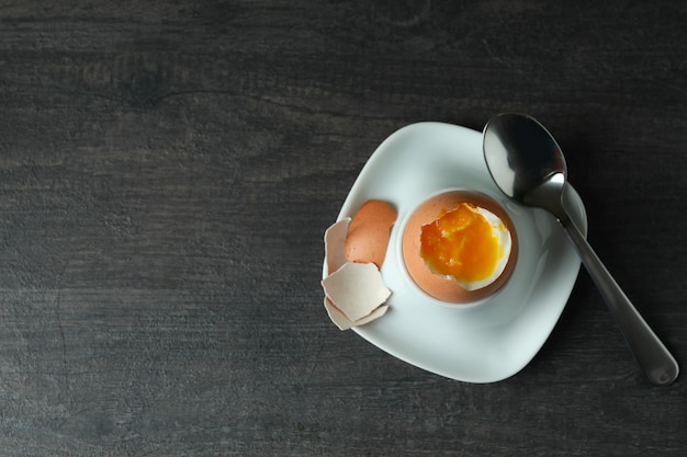 Concept of tasty breakfast with boiled egg on dark wooden table