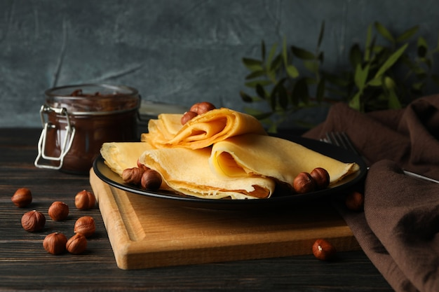 Concept of tasty breakfast with crepes with nuts and chocolate paste on wooden table
