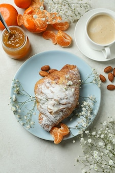 Concept of tasty breakfast with croissant, mandarin jam and coffee on white textured table