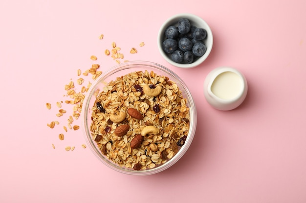 Concept of tasty breakfast with granola on pink background