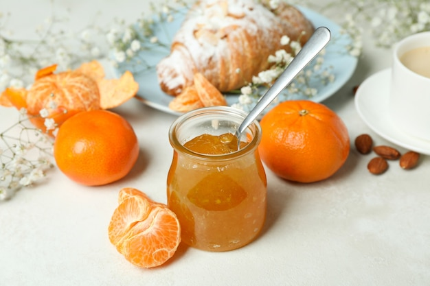 Concept of tasty breakfast with mandarin jam on white textured table